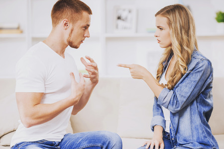 Young Couple Arguing on Soft Couch at Sweet Home. Family Relations. Cute Girl Points Finger at Her Boyfriend. Destruction of Relationships Before Eyes. Very Unpleasant Family Quarrel.