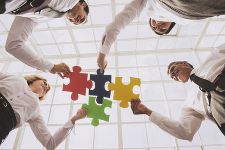 Group of Business People Assembling Jigsaw Puzzle. Team Building Activities. Bottom View. Four Smart Cute Business Partners in Office. Teambuilding Teamwork and Cooperation Concept.