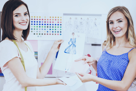 Beautiful and happy designers sitting in studio and demonstrating their sketch. Working on new collection together.