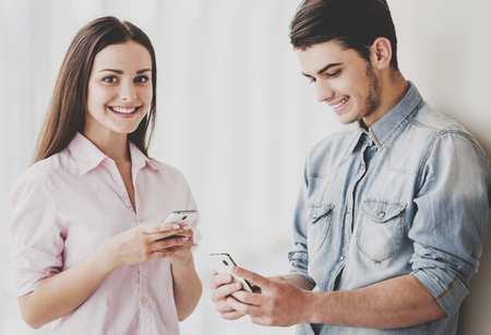 Two Beautiful Young Students Standing Together and Looking at Their Gadgets Indoors. Funny Students Years. Girl Looking at Camera and Smiling. Handsome Happy Guy Uses Digital Tablet.