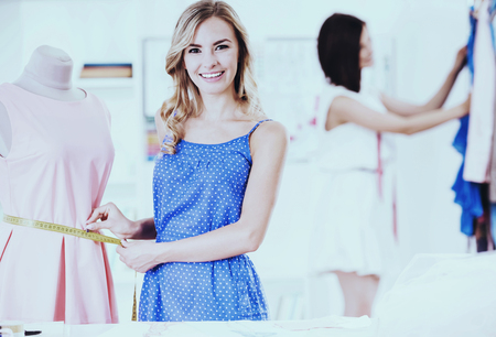 Two Young Clothing Designer Working with Fabric in Sewing Design Showroom. Small Business. Young Beautiful Woman in Blue Dress Looking at Camera and Smiling. Modern Fashion Workplace. Stock Photo