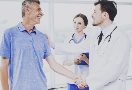 Patient and his Confident Doctor Shake Hands. Successful Treatment of Happy Patients. Healthcare Concept. Friendly Professional Male Doctor Talking with Elderly Sick Man in Hospital.