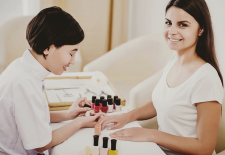Happy Asian Professional Customer Doing Manicure. Cheerful Happy Cute Manicurist Looks at Client Hands and Smiles. Professional Manicure. Nail Polish Concept. Care of Hands and Nails. Stock Photo