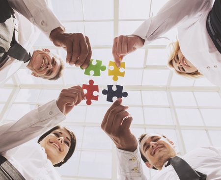 Businessmen Holding and Putting Puzzle Pieces Together. Teamwork and Cooperation Concept. Bottom View. Four Smart Cute Business Partners in Office. Teambuilding Teamwork and Cooperation Concept. Standard-Bild