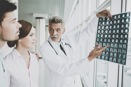 Tense Male Doctor Indicates on Image of Roentgen. Showing Patients Results at Diagnostic Centre. Rapid Improvement. Doctors and Patients Discuss in Clinic. Professional in Coat with Stethoscopes. Banco de Imagens - 104541532