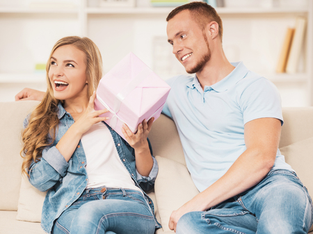 Man Giving Box with Present to Cheerful Girlfriend. Beautiful Unexpected Surprise. Happy Relationships. Family Idyll. Establishing Relations. Healthy Happy Family Relationships Concept. Stock Photo