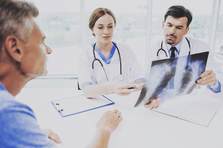 Doctors and Patients Discuss Roentgen Images in Diagnostic Center. Doctors with Stethoscopes at Table. Male Doctor Indicates on Image Roentgen. Showing Patients Results at Clinic. Rapid Improvement. Banco de Imagens - 104541548