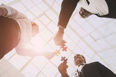 Three Smart Business Partners with Jigsaw Puzzles. Closeup of Business People Wanting Put Three Pieces of Puzzle Together. Team Work. Bottom View. Teambuilding Teamwork and Cooperation Concept.