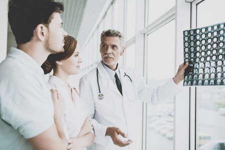 Médecin de sexe masculin tendu indique sur l'image de Roentgen. Affichage des résultats des patients au centre de diagnostic. Amélioration rapide. Les médecins et les patients discutent en clinique. Professionnel en manteau avec stéthoscopes. Banque d'images - 104541558