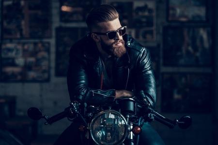 Jeune motard barbu assis sur la moto dans le garage. Garage intérieur. Jeune mécanicien au garage. Pièces de moto. Homme en chemise à carreaux. Homme sur vélo vintage. Concept de style de vie de motard.