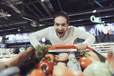 Excited Man with Shopping Trolley in Supermarket. Shopping Cart with Food. Active Shopping. Consumerism Concept. Man in Shirt. Shopping in Supermarket. Vegaterian and Healthy Food Concept.