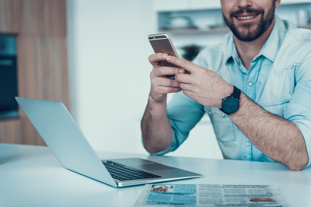 Close up. Beaded Man with Phone and Laptop in Dining Room. White Table in Dining Room. Hand Watch. Using Cell Phone. Businessman at Home. Bearded Man with Digital Device. Man Using Smartphone.