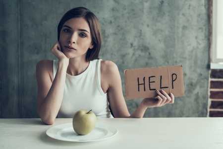 Young Woman with Sign Help and Eating One Apple. Diet Concept. Weight Loss Problem. Starving Young Woman. One Apple on White Plate. Hungry Woman. Healthy Lifestyle Concept. Starving Vegetarian.