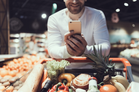 De cerca. Hombre que usa el teléfono celular cerca de la carretilla de la compra. Padre con carrito de compras. Carro de compras con comida. Concepto de consumismo. Hombre de camisa. Compras en el supermercado. Dispositivo digital.