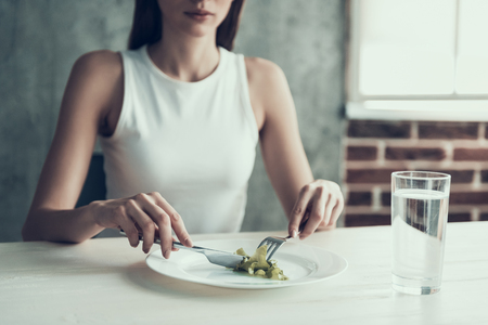 Woman Sitting on Chair and Eating Salad on Plate. Diet Concept. Weight Loss Problem. Starving Young Woman. Fork and Knife. Hungry Woman. Healthy Lifestyle Concept. Starving Vegetarian. Stock Photo
