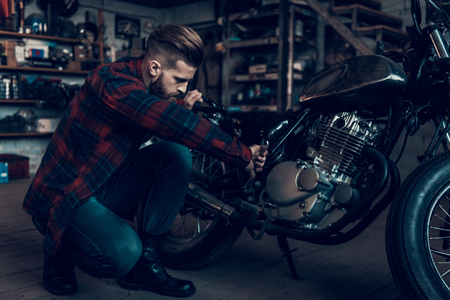 Young Bearded Biker Tuning Motorcycle in Garage. Indoor Garage. Young Mechanic in Garage. Parts of Motorcycle. Man in Checkered Shirt. Man and Vintage Bike. Biker Lifestyle Concept. Stock Photo