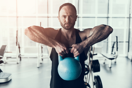 Bearded Young Man in Shirt Training in Fitness Club. Man with Athletic Body. Healthy Lifestyle and Sport Concepts. Young Man in Training Club. Active Indoor Training. Sport Equipment.