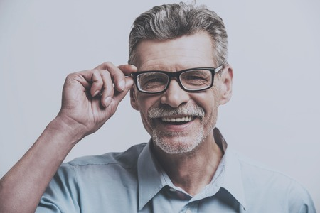 Adult Smiling Man with Glasses. Looks at Camera. Closeup Person. Isolated Background. Portrait of Joyful European Male. Emotions of Old Man. Pointig Professional Portrait. Handsome Trendy Photography.