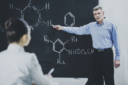 Teacher Leading Lecture in University Classroom. Professor ask Student About Chemistry Formula. Educational Concept. Explanation for Students. Academic Blackboard. Chemistry College.