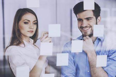 Two Managers Think Aabout Presentation of Startup. Stickers on Glass. Business Concept. Productive Employeers. Project Makers in Office. Partners Thinking in Office. Draw a New Productivity Plan. Standard-Bild - 105263684