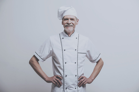 Chef Cooker with Hands on Belt. Male Kitchener Uniform. Isolated Background. Cooking Concept. Kitchenware Lifestyle. Culinary Job Concept. Professional Staff. Old Person at Work. Working Process. Stock Photo