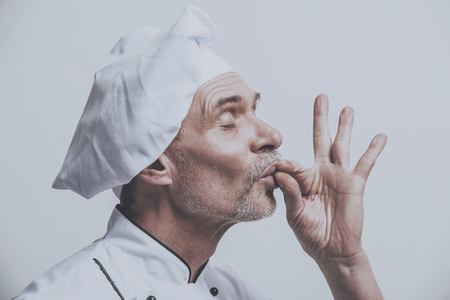 Satisfied Chef Cheeks Fingers. White Male Gourmet. Cooking Concept. Isolated Background. Profile Photo. Closeup Old Man. Kitchen Uniform. Professional Resturant Photo. Working Process. Stock Photo