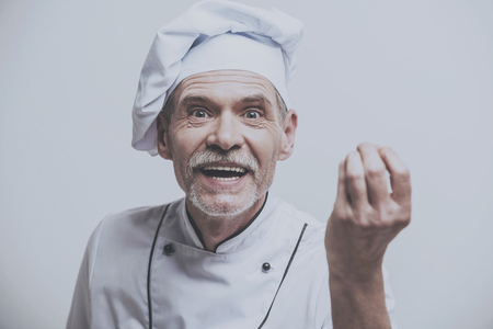 Chef With Hand in Foreground. Looking at Camera. Male Cooker. Kitchen Uniform. Isolated Grey Background. Closeup Portrait Photo. Old Man on Uniform. Emotional Worker. Happy Chef Background.