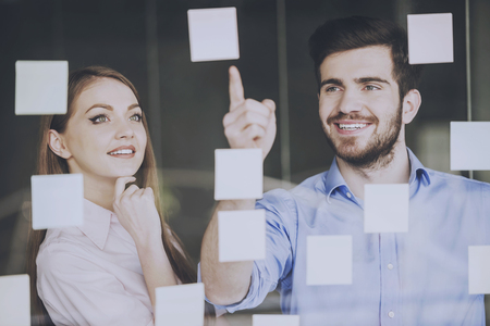 Manager Shows Collegue How to Improve New Project. Stickers on Glass. Business Concept. Attractive People. Young Emploees at Work. Startup Graphic. Efficiency Coworking. Collegues Write Buisness Idea. Standard-Bild - 105389599