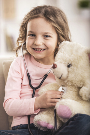 Little Girl Playing Doctor with Teddy Bear. Cute Baby with Toy. Family Concept. Smiling Girl. Baby Looking on Camera. Healthcare Concept. Cheerful Person Background. Pretty Small Child.