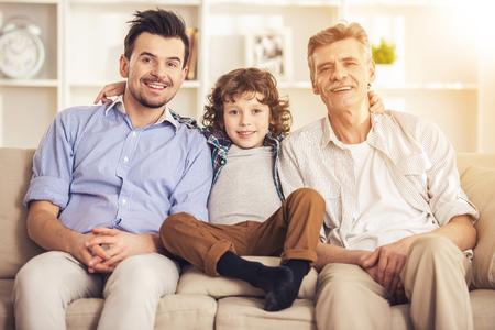 Heureuse génération de trois hommes. Assis sur un canapé. Grand-père père et fils. Regarder à la caméra. Portrait de famille. Concept de famille. Portrait photo professionnel. Trois personnes. Enfant avec les hommes les plus âgés.