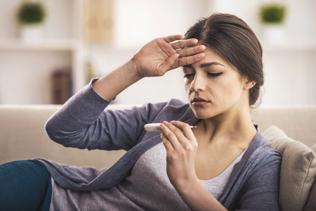 Female is Measuring Temperature. Young Woman Looking at Thermometer. Touches Forehead. Bad feeling. Disease of Young European. Healthcare Concept. Sikness Woman. Sad Suffering Person. Stok Fotoğraf