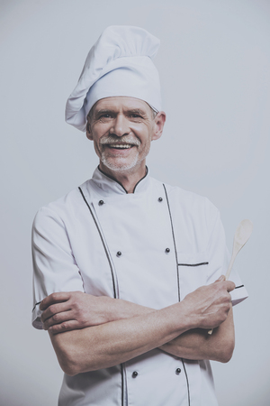 Portrait of Happy Male Chef Cook. Arms Folded. Kitchenware Portrait Photo. Isolated Background. Male Kitchener. Kitchen Uniform. Cooking Professional Concept. Smiling Restaurant Worker.
