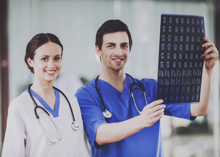 Two Young Surgeons Carefully Examine X-ray Scan in Hospital. Work in Clinic. Concept of Health Care. Medical Consultant. Holding Scan. Clinical Concept. Standing in Hospital. People in Uniform. Stock Photo - 105587403
