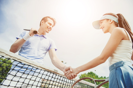 Couple Shakes Hands with each other after Tennis Match Between them.Recreation Concept. Family Leisure. Caucasian Couple. Training Together. Practice Sport with Girlfriend. Athletic Couple. Foto de archivo - 105658395