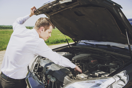 Worried Young Businessman Examining Broken Car Engine at Countryside.Road Accident. Man Businessman Repair Broken Vehicle. Portrait of Person with Trouble. Collision Accident. Break Down. 版權商用圖片