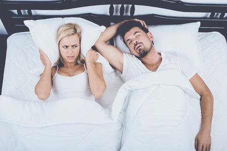 Top View of Man Snoring Loudly Wife Blocks Ears. Snore Concept. Snore, Sleep, Apnea, Couple in Love, Sleep Concept