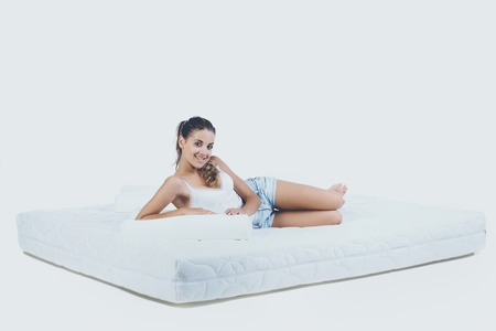 Young Smiling Woman Lying on Orthopedic Mattress. Isolated on White Background. Healthy Concept.
