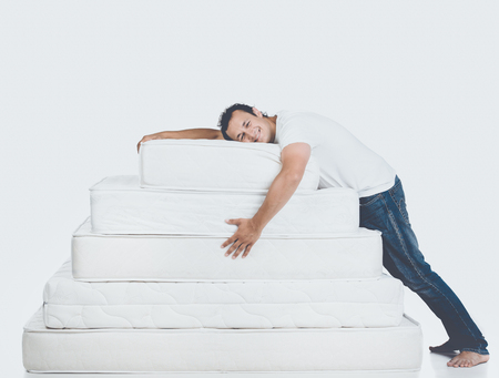 Smiling Man Lying on Pyramid of Mattress. Isolated on White Background. Healthy Concept.
