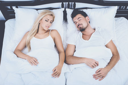 Top View of Young Couple Sleeping in Bed at Home. Healthy Sleep Concept. Snore, Sleep, Apnea, Couple in Love, Sleep Concept