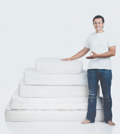 Smiling Man Standing Near Pyramid of Mattress. Isolated on White Background. Healthy Concept.