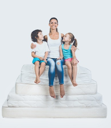 Kids with Mother Sitting on Pyramid of Mattress. Mom Hugging Son and Daughter. Isolated on White Background. Healthy, Family Concept. Banque d'images