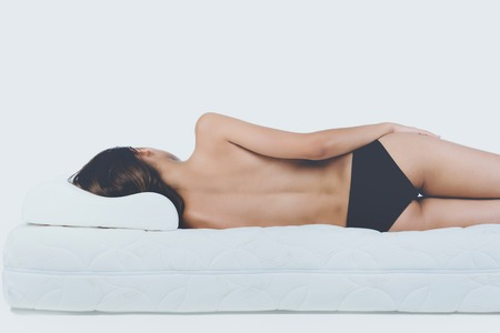 Young Bare Woman Lying on Orthopedic Mattress. Isolated on White Background. Healthy Concept. Stockfoto