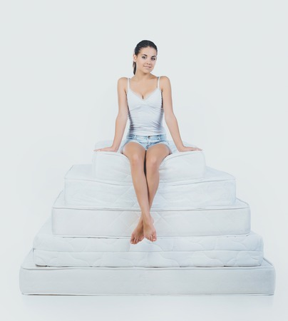 Young Smiling Woman Sitting on Pyramid of Mattress. Pretty Girl Sitting on top of Pyramid of Orthopedic Mattress. Isolated on White Background. Healthy Concept.
