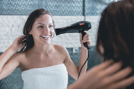 Young Girl Dries Hair Dryer After Showering in Bathroom. Brunette Wrapped in Towel after Taking Bath makes Care of Body. Beauty Concept. Personal Hygiene at Morning. Beautiful Woman at Morning. Banco de Imagens