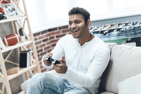 Young Indian Man Fascinated by Game on Console. Guy during Rest has Joystick in Hands from Console. Time to Relax Concept. Handsome Happy Guy on White Sofa While Win in Video Game.