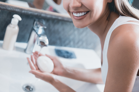 Close up. Young Girl Standing in Front of Mirror in Bathroom Cleaning Arms with Soap. Care Beauty Concept. Female Hygiene Concept. Everyday Routine. Daily Hygiene. Beautiful Woman.