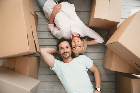 Top View. Adult Happy Family Lying Side by Side on Floor. Around lot of Cardboard Boxes. Family Couple Smiles while Collecting Things. Concept Housing Family. Young Man in Room. New Apartment Concept.