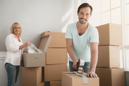 Packing Boxes with Building Tape in Order to Move to New Housing. Moving the Family to New Place. Family Gathers Things in Cardboard Boxes. Young Family in Room. New Apartment Concepts. Stock Photo