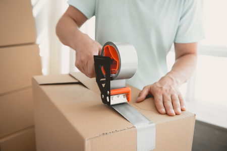 Close up. Packing Boxes with Building Tape in Order to Move to New Housing. Moving the Family to New Place. Family Gathers Things in Cardboard Boxes. Young Man in Room. New Apartment Concepts.
