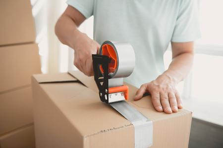 クローズアップ。新しい住宅に移動するために、建物のテープを持つ梱包箱。家族を新しい場所に移動する。家族は段ボール箱に物を集める。部屋の若い男。新しいアパートの概念。